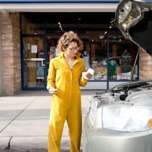 Lane in the Thelma Boilersuit checking car oil
