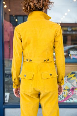 The back of a person in the Thelma Boilersuit showing off their buttons.
